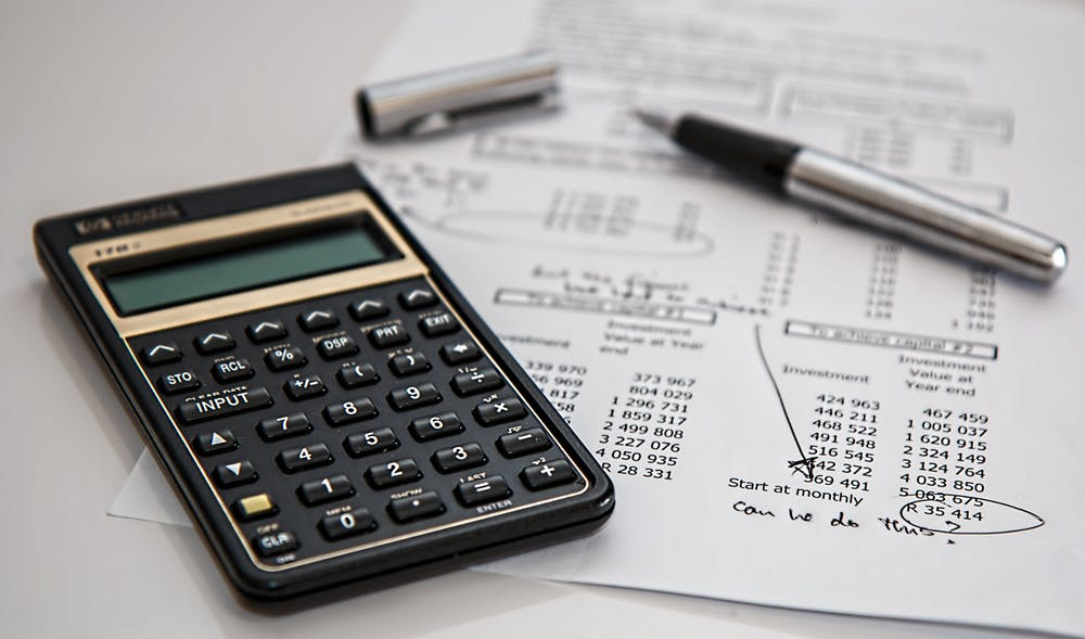 Calculator and Pen Resting on Financial Statements